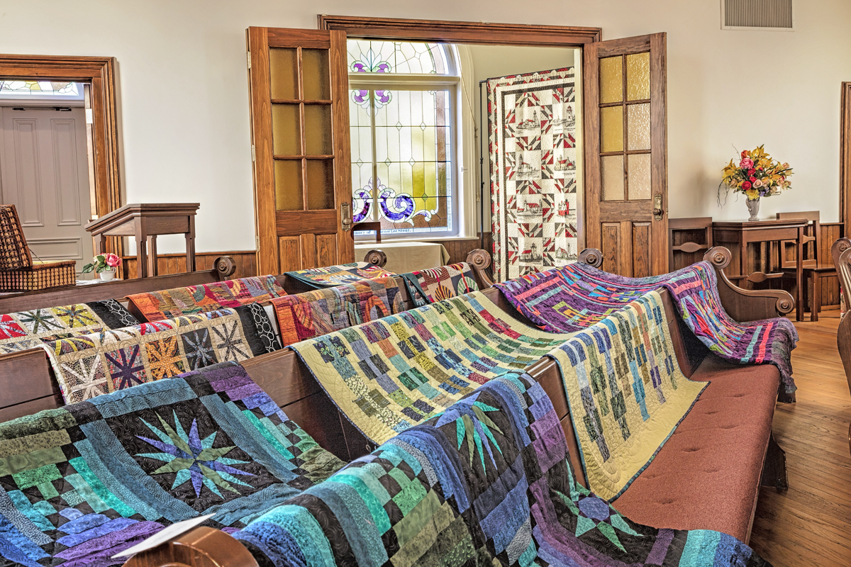Threads Quilts featured in the Church Bell Room over the pews.