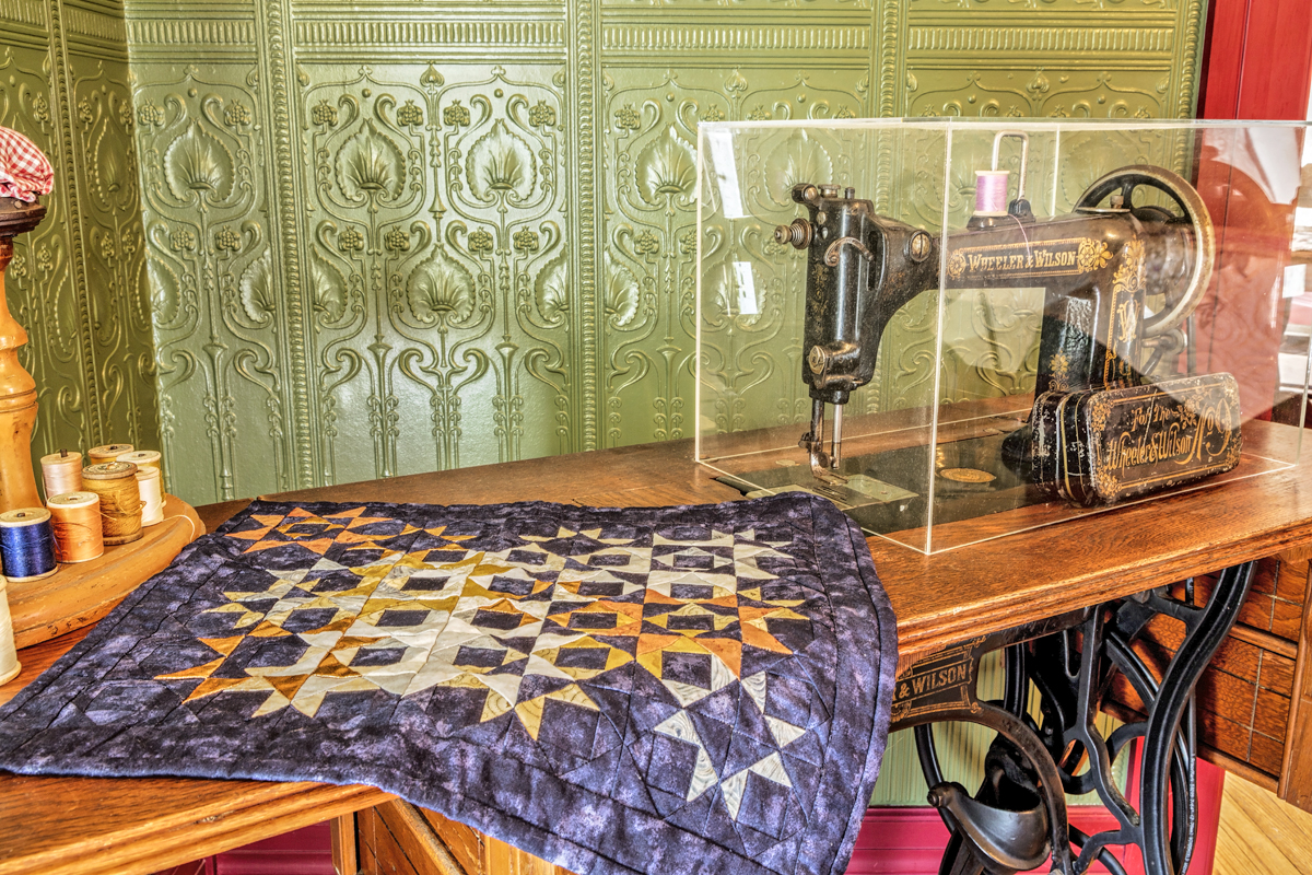 Threads Quilts Exhibit in the Parsonage with Wheeler Wilson Sewing Machine Quilt.